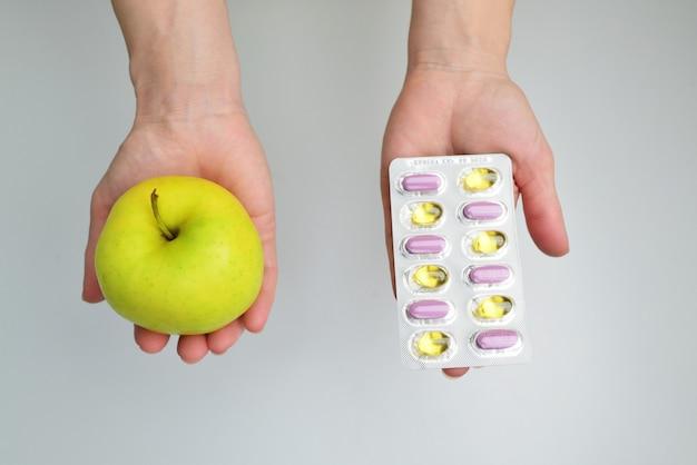 Vue supérieure des mains en gros plan montrant une pomme dans une main et des pilules pharmaceutiques dans une autre