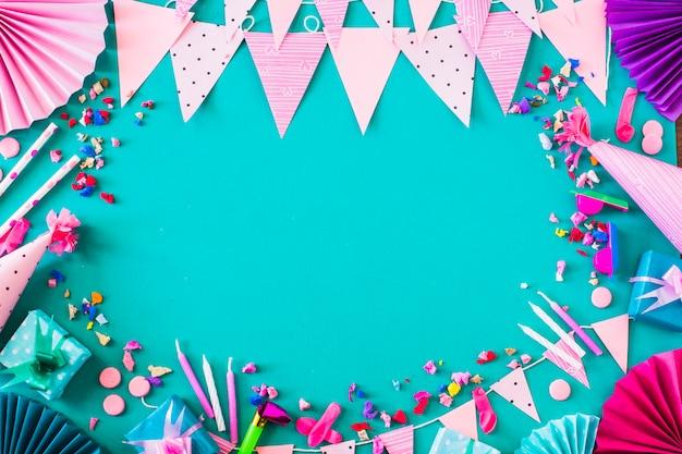Vue surélevée de coffrets cadeaux et divers accessoires de fête sur fond vert