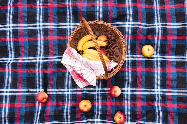 Une vue surélevée du panier de pique-nique avec des bananes et des pommes sur une couverture