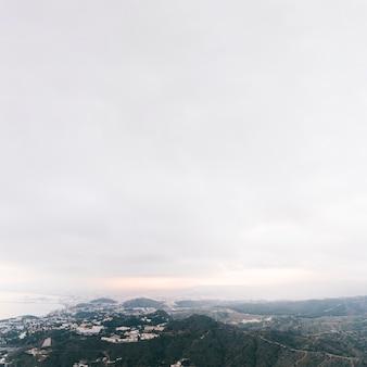 Une vue surélevée du paysage de montagne de campagne avec un ciel nuageux blanc