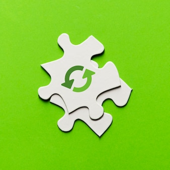 Vue surélevée d'icône de recyclage sur la pièce de puzzle blanche sur fond vert