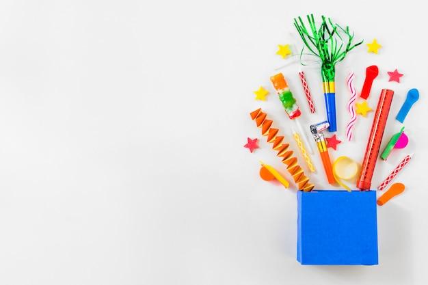 Vue surélevée de sac en papier avec divers accessoires de fête sur fond bleu