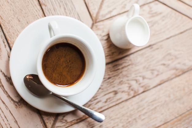 Vue surélevée d'une tasse de café savoureuse et d'un pot à lait en céramique