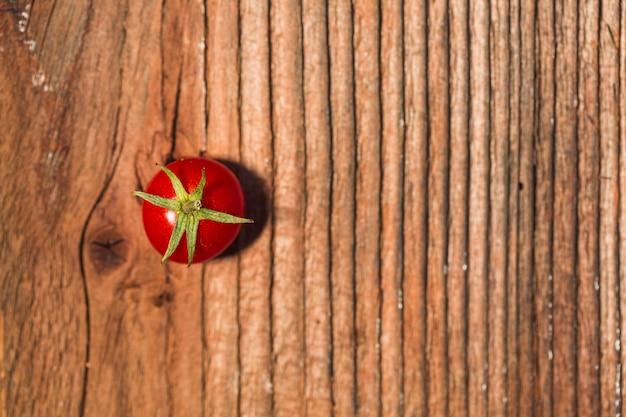 Vue surélevée de tomate cerise rouge juteuse sur fond en bois