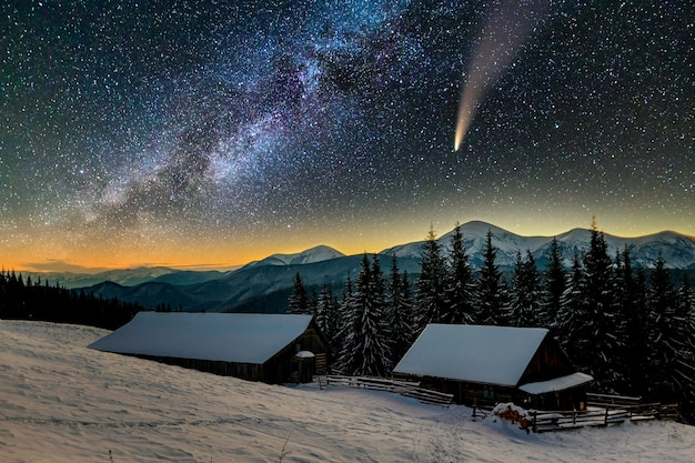 Vue surréaliste de la nuit dans les montagnes avec ciel nuageux bleu foncé étoilé et comète c / 2020 f3 (neowise) avec queue légère.