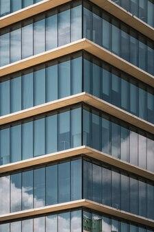 Vue symétrique de l'angle d'un immeuble de bureaux avec fenêtres vitrées verticales