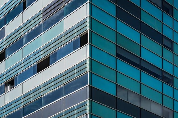 Vue symétrique de l'angle d'un immeuble résidentiel avec des rangées de fenêtres bleuâtres et verdâtres