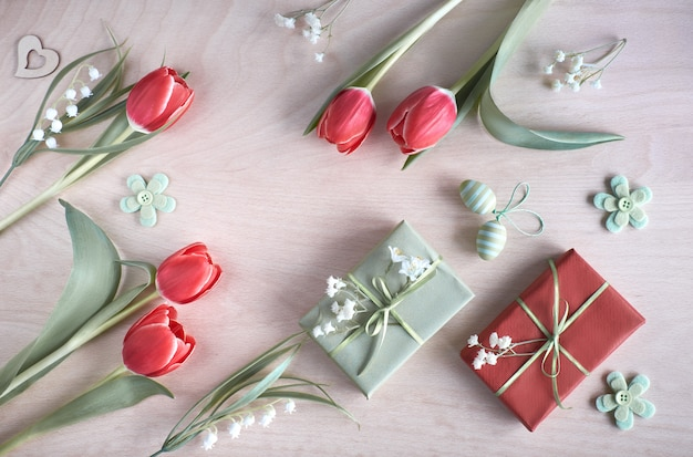 Vue de la table en bois clair avec des décorations de printemps, des cadeaux emballés, des fleurs blanches, des tulipes rouges et des oeufs de pâques