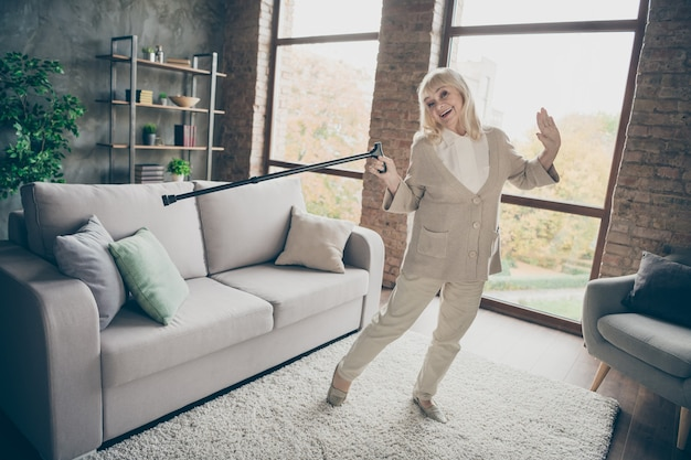 Vue de la taille du corps sur toute la longueur de belle belle bonne santé joyeuse joyeuse joyeuse grand-mère aux cheveux gris dansant avec canne s'amusant à la retraite à l'intérieur de style moderne loft en brique industrielle
