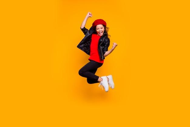 Vue de la taille du corps sur toute la longueur d'elle elle belle attrayante à la mode gaie joyeuse funky brune fille aux cheveux ondulés sautant se réjouir de s'amuser isolé sur un mur de couleur jaune vif brillant