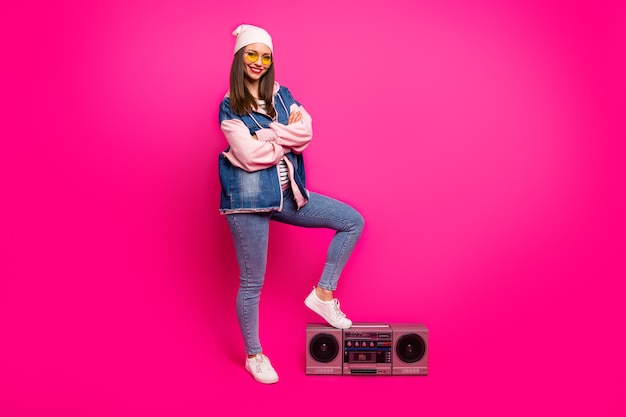 Vue de la taille du corps sur toute la longueur d'elle, elle belle séduisante fille joyeuse et joyeuse séduisante mettant la jambe sur boom-box s'amusant vacances isolées sur la couleur fuchsia rose vif brillant éclatant