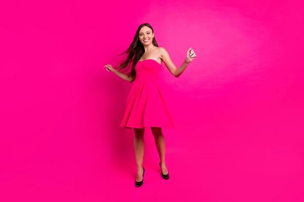 Vue de la taille du corps sur toute la longueur d'elle, elle est belle et attrayante, magnifique, coupe mince, mince, joyeuse, longue fille aux cheveux longs, s'amusant, isolé sur fond de couleur rose fuchsia brillant vif éclatant