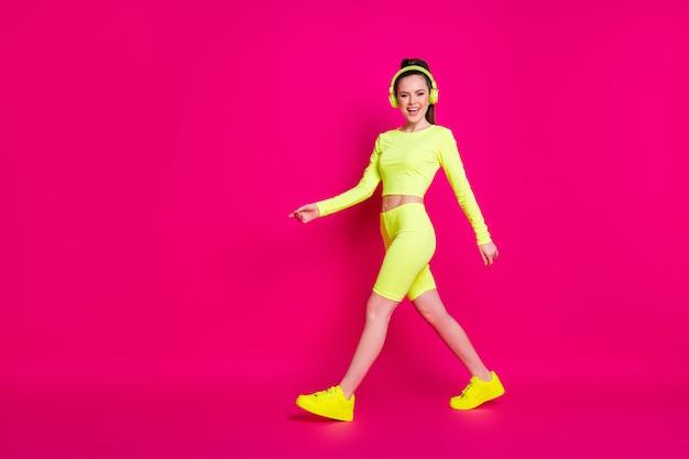 Vue de la taille du corps sur toute la longueur d'elle, elle est belle, mince, mince, sportive, joyeuse, joyeuse, écoutant différentes musiques pop marchant isolées, brillantes, brillantes, éclatantes, fond de couleur rose fuchsia