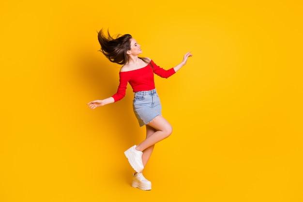 Vue de la taille du corps sur toute la longueur d'elle, elle est jolie, jolie, jolie fille mince et gaie, danse s'amusant du temps libre, isolée, brillante, éclatante, fond de couleur jaune vif