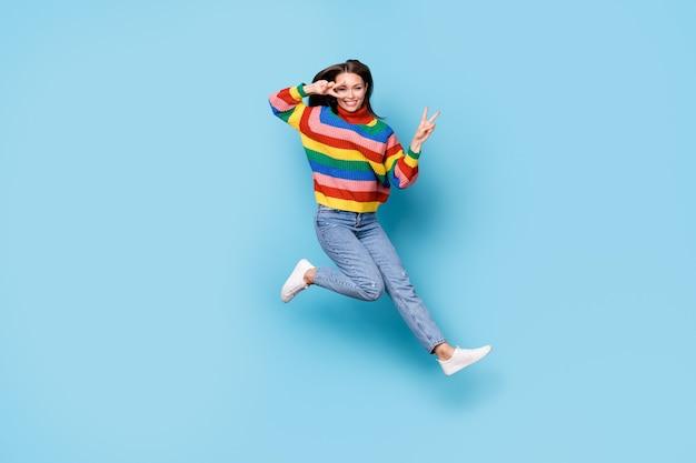 Vue de la taille du corps sur toute la longueur d'elle, elle est jolie, jolie, jolie, jolie, gaie, joyeuse, gaie, sautant en s'amusant en montrant l'heure de la fête du signe v isolé sur fond de couleur pastel bleu
