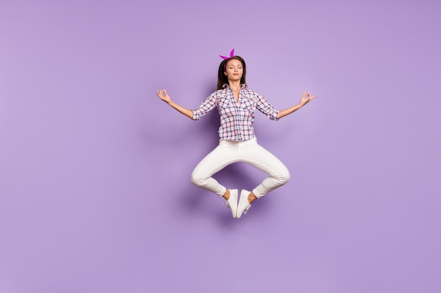 Vue de la taille du corps sur toute la longueur d'une fille calme sautant en méditant