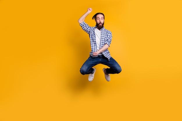 Vue de la taille du corps sur toute la longueur de nice funky gai barbu en chemise à carreaux sautant