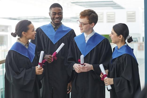 Vue de taille sur un groupe diversifié de jeunes portant des robes de graduation à l'intérieur dans un intérieur universitaire moderne et discutant