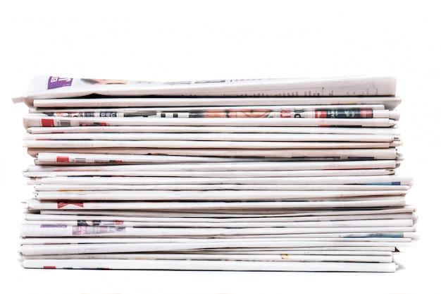 Vue d'un tas de journaux empilés isolé sur fond blanc.