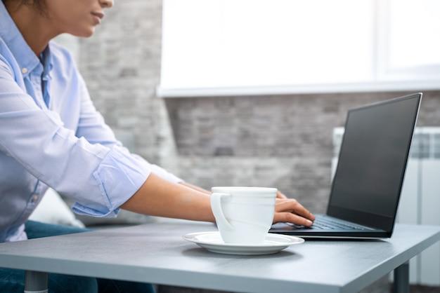 La vue d'une tasse à côté d'une femme travaillant sur un ordinateur portable. travail à distance de la maison.