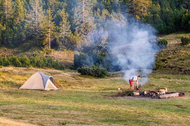 Vue avec une tente, feu de camping avec fumée et randonneur touristique en journée d'été.