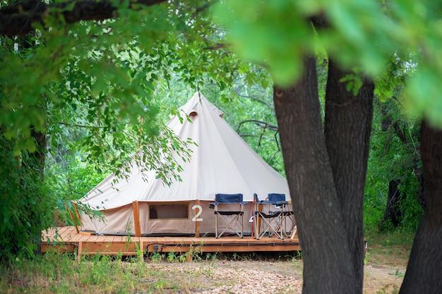 Vue des tentes de camping modernes dans la zone de glamping. tente de camping avec toutes les commodités. civilisation dans la forêt