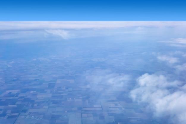 Vue de la terre avec des champs cultivés à travers les nuages et la brume atmosphérique