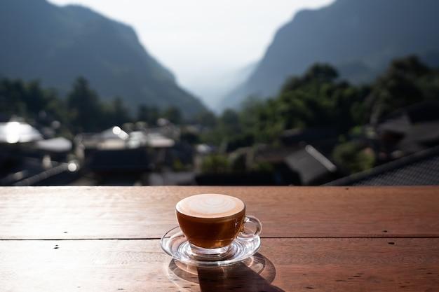Vue sur le thé au lait chaud art latte sur table en bois avec paysage relaxant à pha hee village, chiang rai, thaïlande