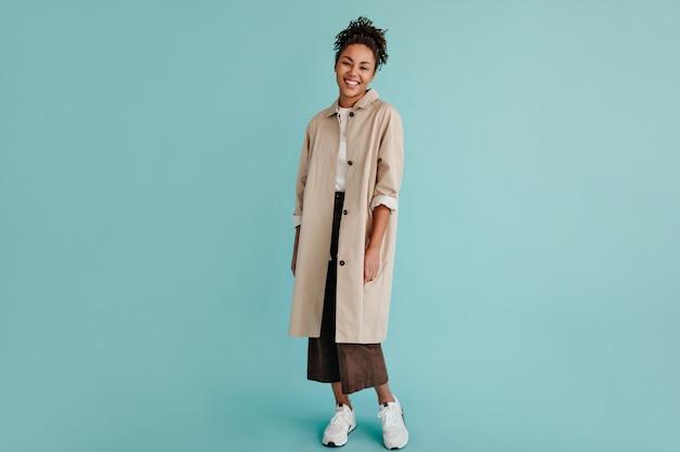 Vue sur toute la longueur de l'adorable femme en trench-coat