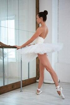 Vue sur toute la longueur de la ballerine gracieuse debout à la barre à l'école de danse. copyspace