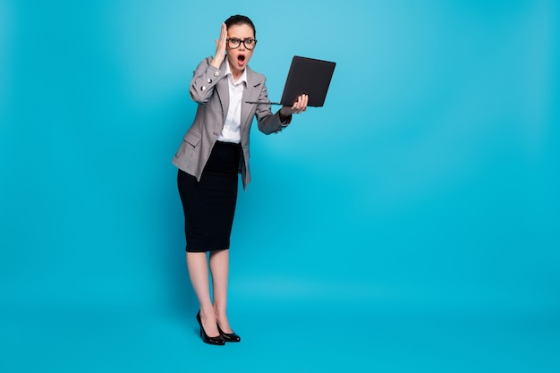 Vue sur toute la longueur du corps d'une belle dame abasourdie spécialiste informatique tenant dans les mains un ordinateur portable omg réaction aux nouvelles isolée sur fond de couleur bleu vif