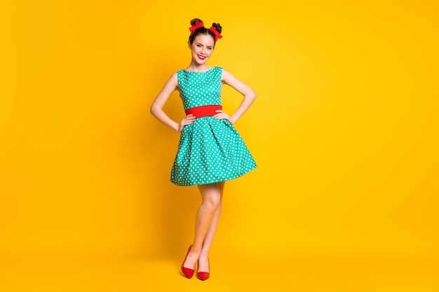 Vue sur toute la longueur du corps d'une belle fille gaie vêtue d'une robe à pois turquoise posant les mains sur les hanches isolées sur fond de couleur jaune vif