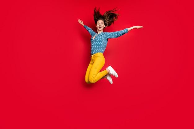 Vue sur toute la longueur du corps d'une belle fille joyeuse et insouciante sautant s'amusant isolé sur fond de couleur rouge vif