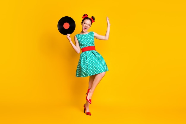 Vue sur toute la longueur du corps d'une belle fille joyeuse tenant dans les mains un disque vinyle dansant s'amusant isolé sur fond de couleur jaune vif