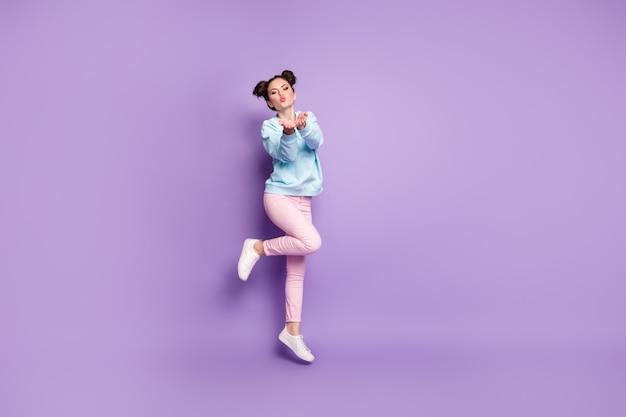 Vue sur toute la longueur du corps d'une belle jolie fille romantique séduisante et séduisante, rêveuse, joyeuse et séduisante, sautant en envoyant un baiser d'air isolé sur un fond de couleur vibrante brillant violet violet lilas brillant éclatant