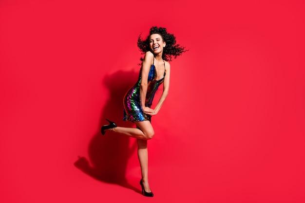 Vue sur toute la longueur du corps d'une charmante fille aux cheveux ondulés gaie posant des cheveux de coup de vent isolés sur fond de couleur rouge vif