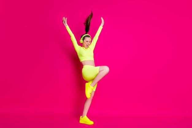 Vue sur toute la longueur du corps d'elle, elle attrayante sportive mince mince fille rêveuse gaie écoutant de la musique s'amusant levant les mains isolées brillantes vives éclat vif fond de couleur rose fuchsia