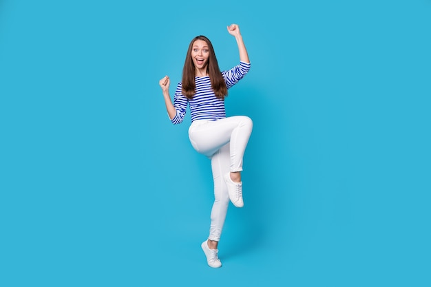 Vue sur toute la longueur du corps d'elle, elle belle jolie fille gaie et gaie portant un saut occasionnel se réjouissant de s'amuser danser isolé sur fond de couleur bleu vif brillant éclatant