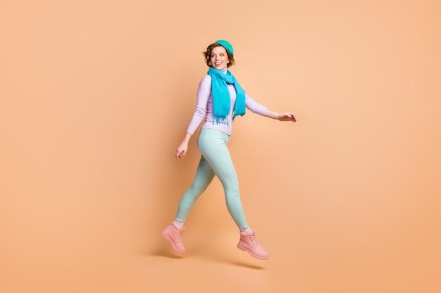 Vue sur toute la longueur du corps d'elle, elle belle jolie jolie fille gaie et gaie sautant en marchant en se promenant portant des vêtements modernes isolés sur fond de couleur pastel beige