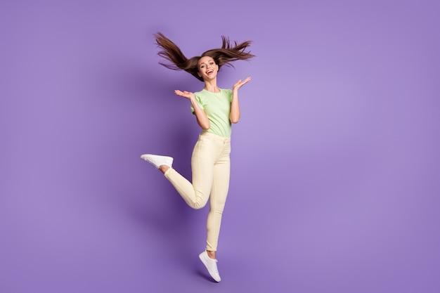 Vue sur toute la longueur du corps d'elle elle belle jolie jolie jolie fille joyeuse joyeuse ravie sautant en s'amusant célébrant isolé brillant vif éclat vibrant fond de couleur violet lilas