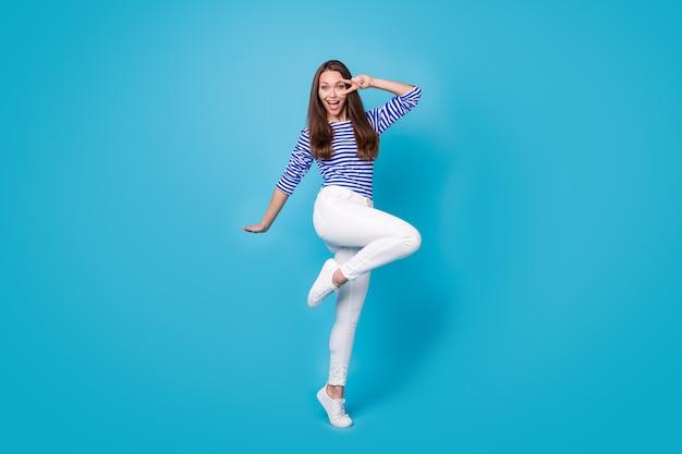 Vue sur toute la longueur du corps d'elle, elle est belle et attirante, joyeuse, joyeuse, joyeuse, gaie, portant un saut décontracté montrant un signe en v dansant isolé sur fond de couleur bleu vif brillant éclatant