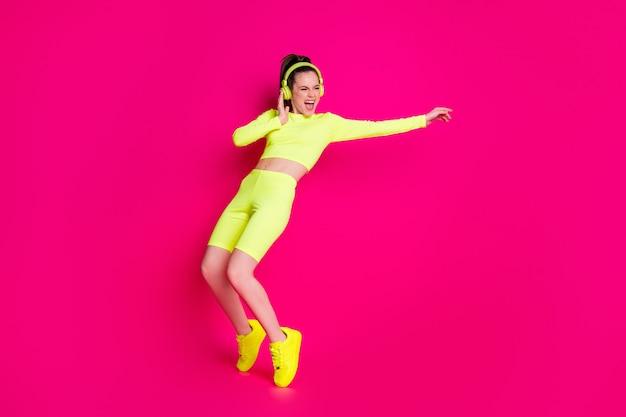 Vue sur toute la longueur du corps d'elle, elle est belle et attirante, mince, sportive, funky, gaie, écoutant de la musique dansant, s'amusant, repos, froid, isolé, brillant, éclat vif, fond de couleur rose fuchsia vibrant