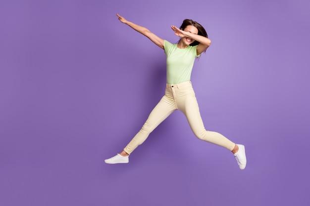 Vue sur toute la longueur du corps d'elle, elle est belle jolie fille gaie, gaie et funky, sautant en s'amusant à danser montrant une touche isolée, brillante, brillante, éclatante, fond de couleur violet lilas vibrant