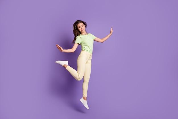 Vue sur toute la longueur du corps d'elle, elle est belle, jolie, gaie, gaie, mince, mince, fille sautant en s'amusant danse de temps libre isolée, brillant, éclat vif, fond de couleur violet lilas vibrant
