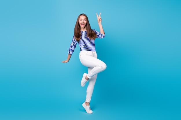 Vue sur toute la longueur du corps d'elle, elle est belle, jolie, jolie, joyeuse, joyeuse, portant un saut décontracté montrant un signe en v s'amusant isolé sur fond de couleur bleu vif brillant éclatant
