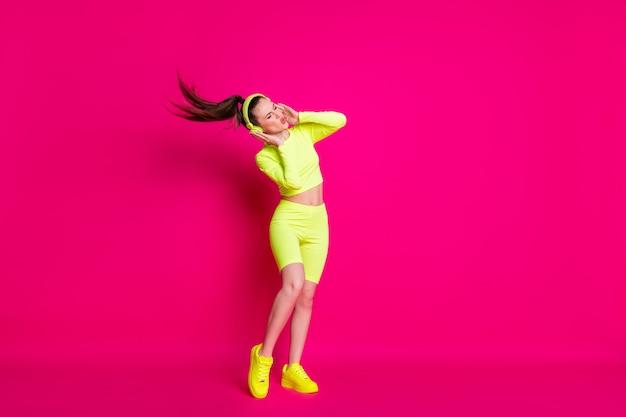 Vue sur toute la longueur du corps d'elle, elle est belle, mince, mince et rêveuse, fille heureuse, écoutant de la musique pop mélodie s'amusant, repos, froid, isolé, vif, brillant, éclatant, fond de couleur rose fuchsia