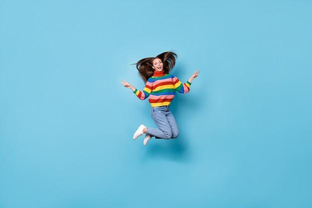 Vue sur toute la longueur du corps d'elle, elle est belle et séduisante, insouciante, géniale et joyeuse, gaie, sautant en s'amusant en montrant le signe v partie de temps libre isolé sur fond de couleur pastel bleu