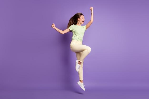 Vue sur toute la longueur du corps d'elle, elle est belle et séduisante, mince, ravie, joyeuse, joyeuse, sautant en se réjouissant de triompher de la victoire, isolée, brillante, éclatante, fond de couleur violet lilas vibrant
