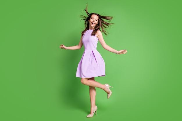 Vue sur toute la longueur du corps d'elle, elle est jolie, jolie, charmante, à la mode, joyeuse, joyeuse, joyeuse, s'amusant à profiter du temps libre des vacances dansant isolé sur fond de couleur verte