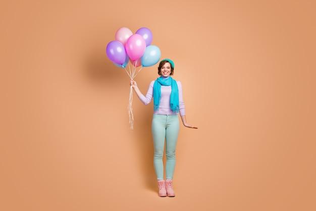 Vue sur toute la longueur du corps d'elle elle jolie jolie jolie jolie charmante contente joyeuse joyeuse fille tenant dans les mains des boules d'air en bouquet isolées sur fond de couleur pastel beige